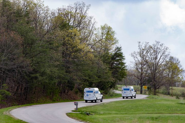 Crime scene investigation vehicles drive up Union Hill Road after bodies of eight family members were found that day at four