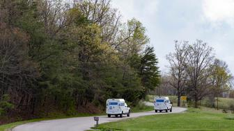 FILE - In this April 22, 2016, file photo, crime scene investigation vehicles drive up Union Hill Road after bodies of eight family members were found that day at four homes in Pike County, Ohio. The victims were shot, some multiple times, but no arrests were made in the two weeks after the killings and the motive remained unclear. (AP Photo/John Minchillo, File)