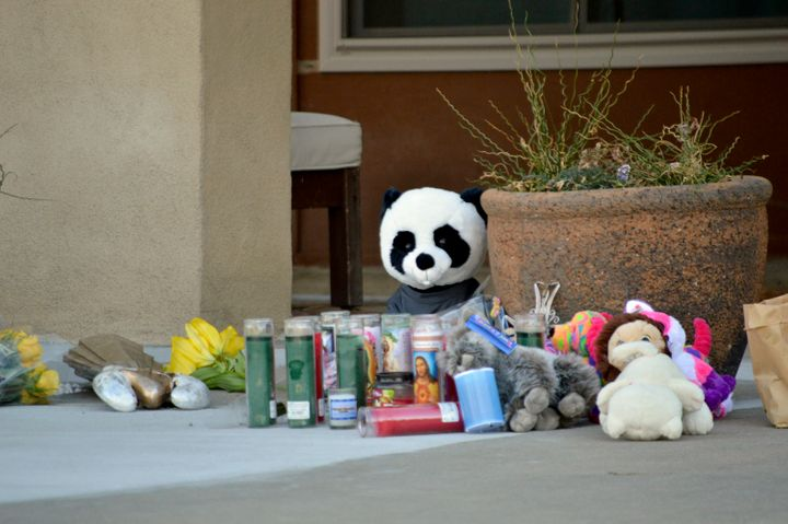 Candles and stuffed animals left by neighbors rest outside an Albuquerque, N.M., home Dec. 7, 2016, after a deadly shooting.