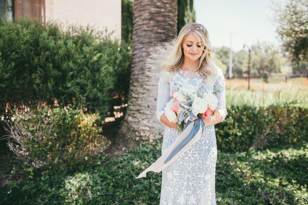 "<i>Gown by <a href=""https://www.moniquelhuillier.com/shop/wedding"" target=""_blank"">Monique Lhuillier</a></i>"