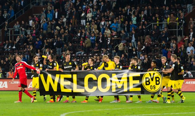 The teams of FC St. Pauli and Borussia Dortmund welcome refugees during the friendly match between FC...