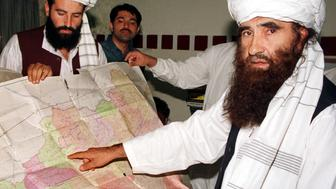 Jalaluddin Haqqani (R), the Taliban's Minister for Tribal Affairs, points to a map of Afghanistan during a visit to Islamabad, Pakistan, October 19, 2001 while his son Naziruddin (L) looks on. One of the pivotal ministers in Afghanistan's ruling Taliban visited Islamabad on Friday, although those who met him said the man responsible for tribal affairs in a country divided along ethnic lines had not defected. Jalaluddin Haqqani arrived in Pakistan on Thursday and visited Islamabad on Friday, although it was not known who he had met, said one source who met the minister. The visit by so senior a Taliban official in the midst of the U.S.-led bombing campaign on Afghanistan has sparked speculation of a split in the hardline movement's ranks.