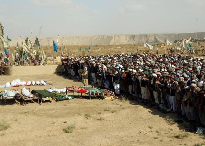Afghans perform prayers at the funeral for the victims killed by an airstrike called in to protect Afghan and U.S. forces dur
