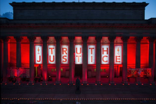 A banner is hung from Liverpool's Saint George's Hall and illuminated in red after a vigil for the 96