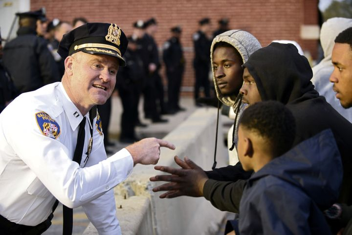 Captain Erik Pecha of the Baltimore Police Department chats with demonstrators in front of the Baltimore Police Department We