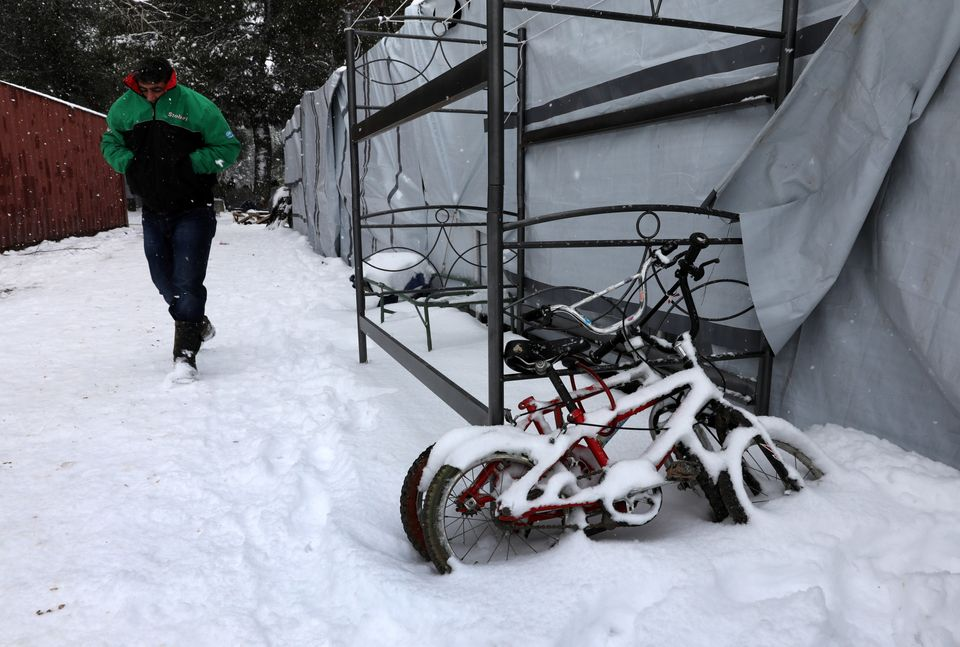 A stranded Syrian refugee braves a snowstorm at a refugee camp north of Athens, Greece.
