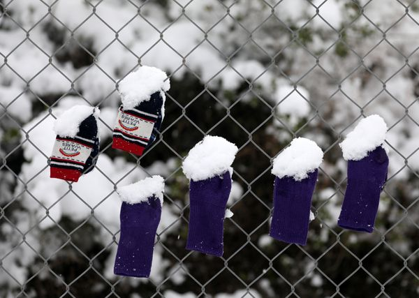 Socks that belong to stranded refugee children are covered in snow.