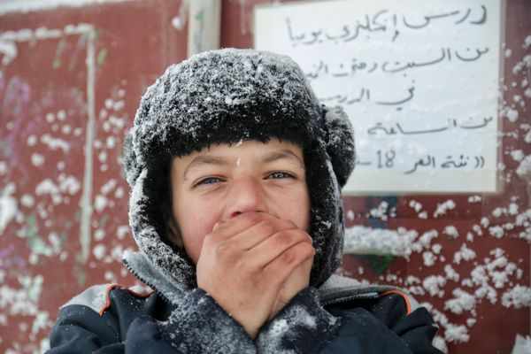 A refugee in the Softex camp, located in northern Greece, tries to stay warm.