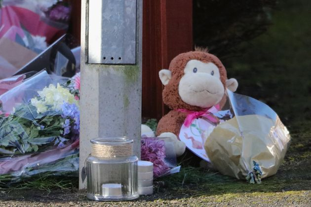 Floral tributes and a teddy bear are left for