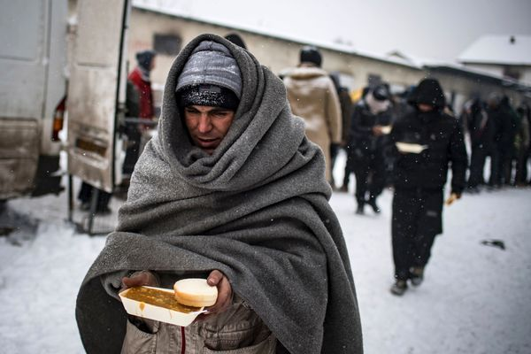 In Belgrade, Serbia, a migrant receives a hot meal in sub-zero temperatures outside of a derelict warehouse being used to she