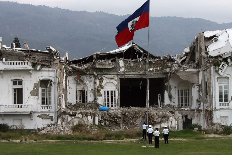 Guards raise the Haitian national flag outside the quake-destroyed ruins of the presidential palace on Nov. 16, 2010.
