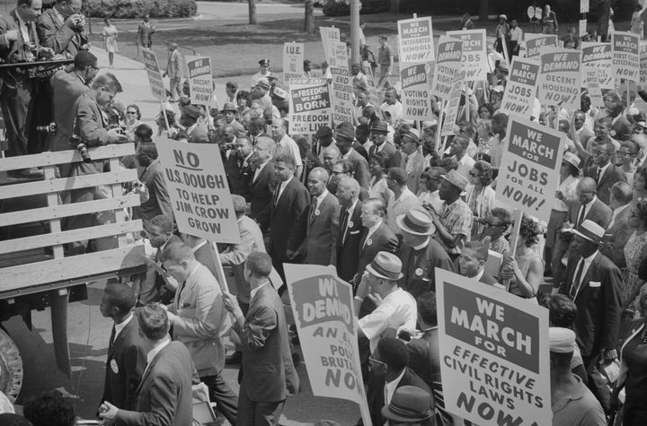 Civil rights leaders, including Martin Luther King, Jr., surrounded by crowds carrying signs, during the civil rights march o