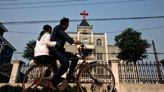 A local resident rides a bicycle past a church in Xiaoshan, a commercial suburb of Hangzhou, the capital of China's east Zhejiang province December 21, 2006. Eight Chinese Christians from Zhejiang province will stand trial on December 22, accused of inciting violent resistance to the law after they protested the government's destruction of a church, a Chinese dissident and a court official said.  REUTERS/Lang Lang (CHINA)