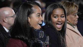Daughters Malia, left, and Sasha Obama smile during the National Christmas Tree lighting ceremony on the Ellipse near the White House in Washington, D.C., U.S., on Thursday, Dec. 3, 2015. In 1923 President Calvin Coolidge lit the first National Christmas Tree, a 48-foot balsam fir tree decorated with 2,500 electric bulbs in red, white and green. Photographer: Olivier Douliery/Bloomberg via Getty Images