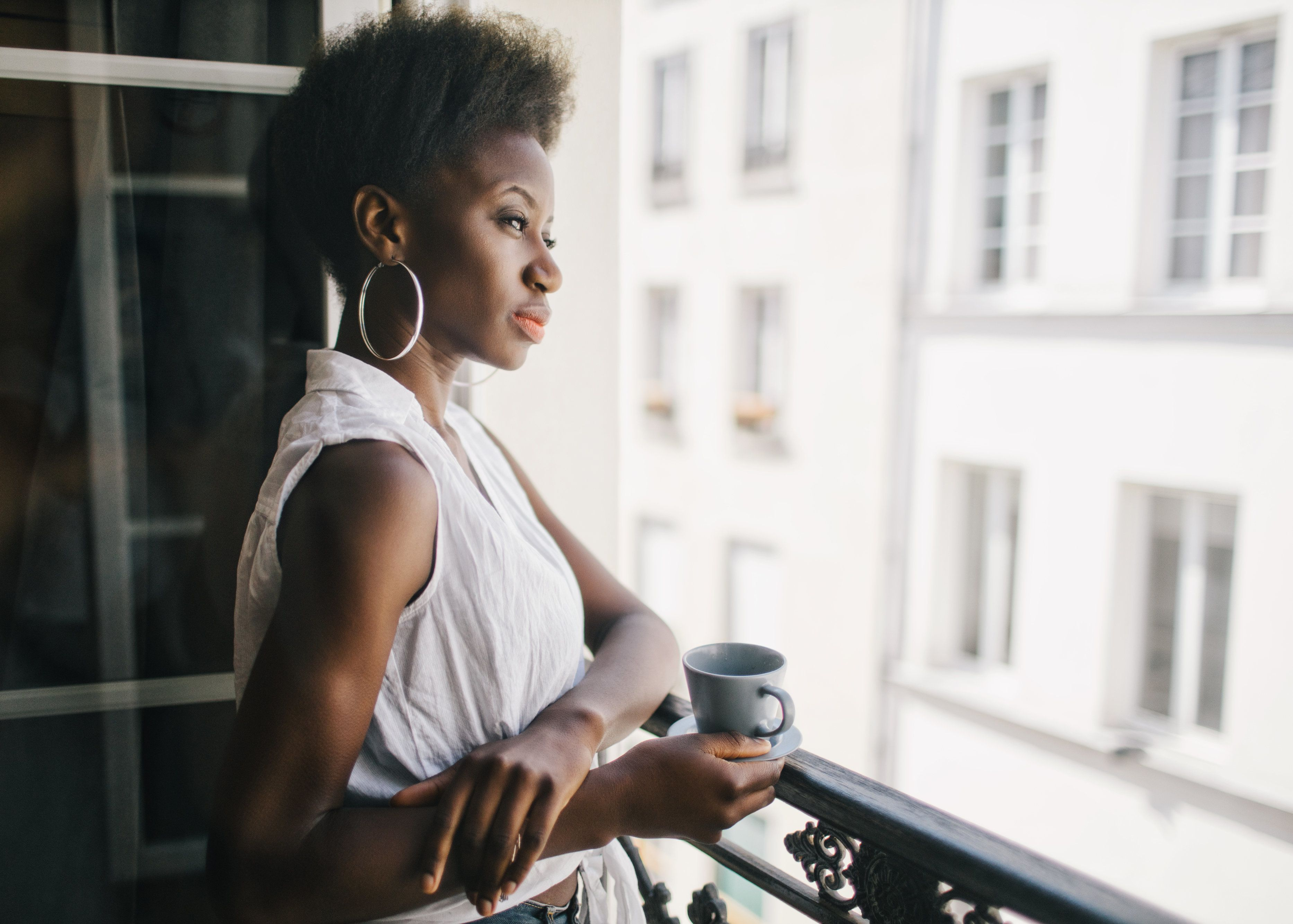 Woman relaxing with a cup of coffee besides the window