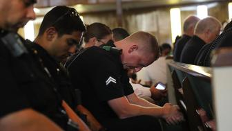 DALLAS, TX - JULY 10:  Police officers from area departments in and around Dallas pray at a multicurtural prayer vigil on July 10, 2016 in Dallas, Texas. The service at the Dallas Area Interfaith Church drew over 100 worshippers including police officers. Five Dallas police officers were killed and seven others were injured last Thursday night in an evening ambush during a march against recent police involved shootings. Investigators say the suspect is 25-year-old Micah Xavier Johnson of Mesquite, Texas. This is the deadliest incident for U.S. law enforcement since September 11.  (Photo by Spencer Platt/Getty Images)