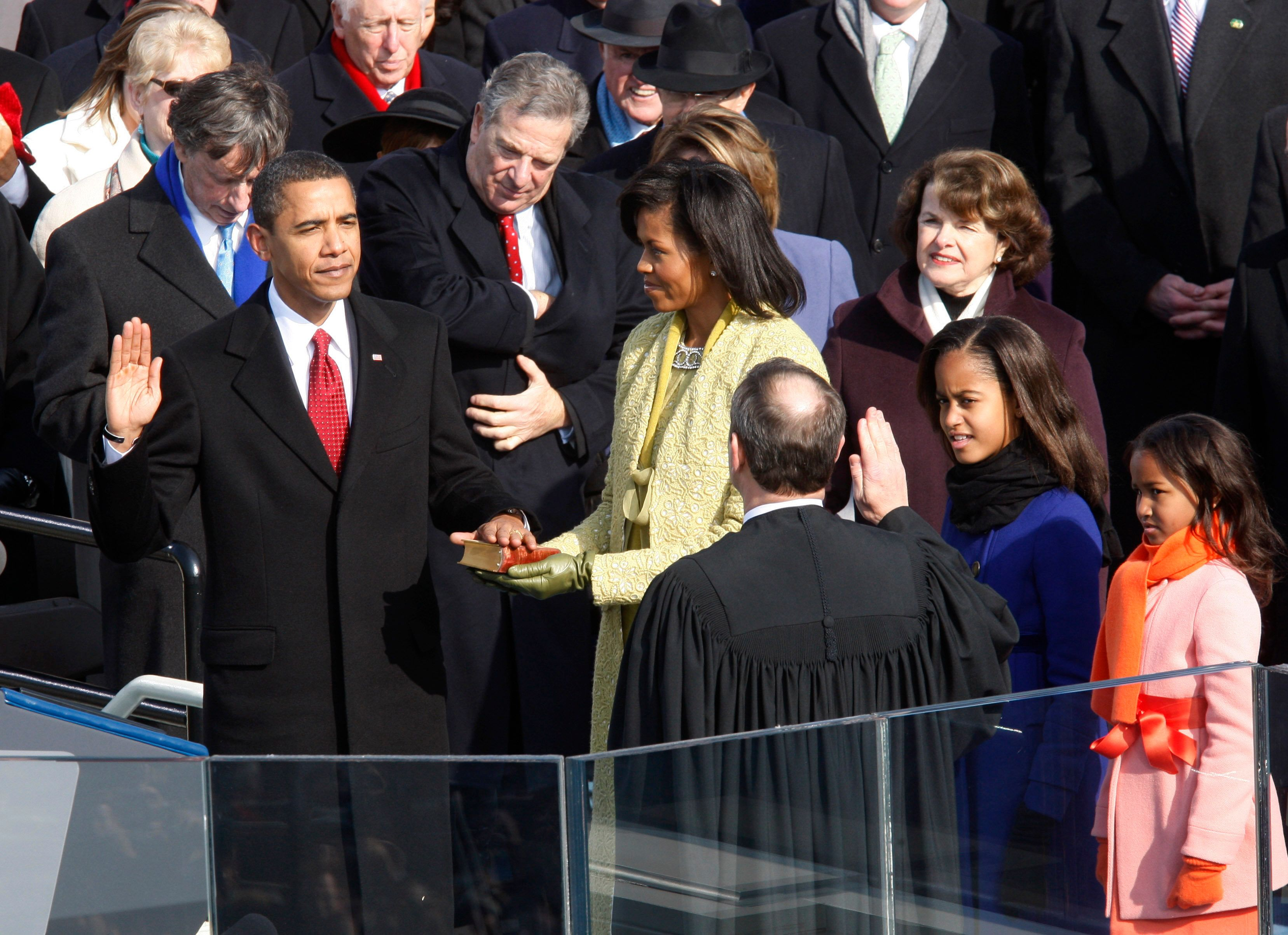 The 44th President of the United States, Barack Obama, takes the oath given by US. Supreme Chief Justice John Roberts, Jr. (lower right) during the inauguration ceremony in Washington, January 20, 2009. Daughters Malia and Sasha (R) look on, as Michelle Obama holds the Bible used by President Abraham Lincoln at his inauguration in 1861.      REUTERS/Jim Bourg (UNITED STATES)