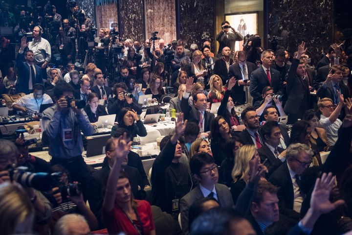 Members of the media raise their hands to try and ask questions as President-elect Donald Trump speaks during a press confere