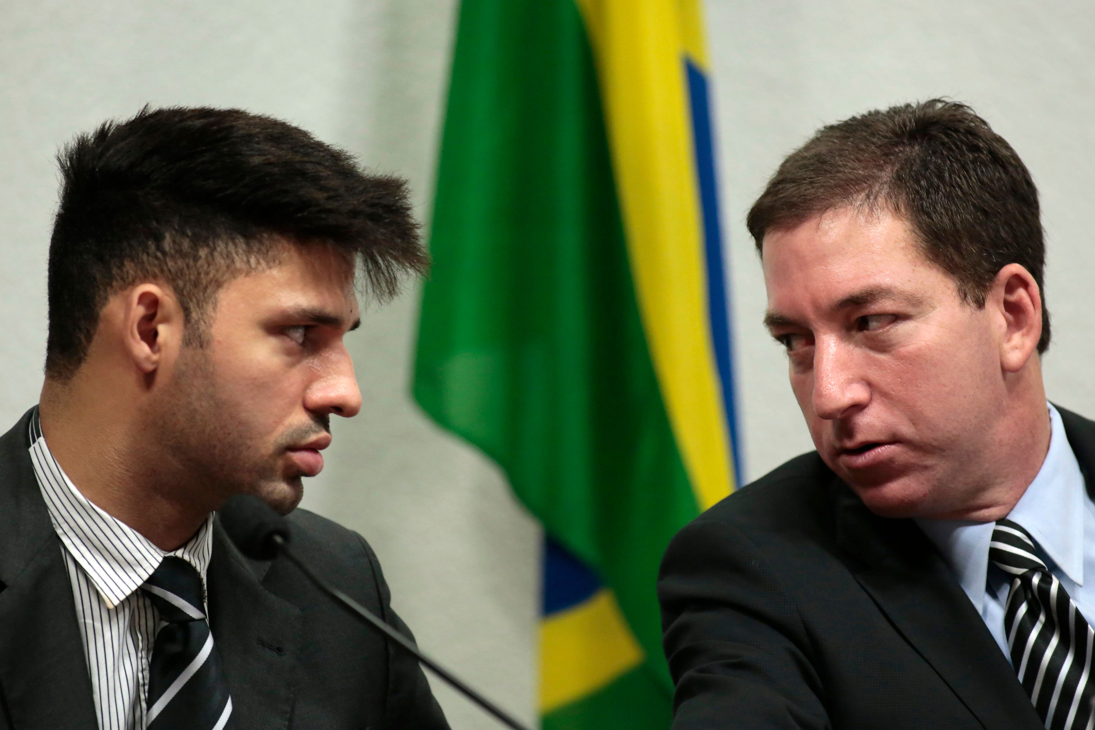Glenn Greenwald (R), American journalist who first published the documents leaked by former NSA contractor Edward Snowden, speaks with partner David Miranda as Greenwald testifies in front of the Brazilian Federal Senate's Parliamentary Inquiry Committee, established to investigate allegations of spying by United States on Brazil, in Brasilia October 9, 2013. REUTERS/Ueslei Marcelino (BRAZIL - Tags: POLITICS MEDIA)