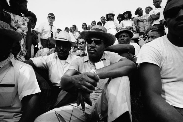 Dr. King  sits with others during a march to encourage voter registration.