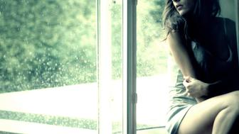 A girl sitting on a window ledge, when it is raining outside.