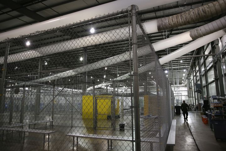 A U.S. Border Patrol agent walks through a detention facility run by the Border Patrol on September 8, 2014 in McAllen, Texas