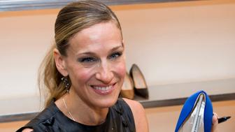 Sarah Jessica Parker autographs shoes at the Manolo Blahnik store as part of Fashion's Night Out in New York, Thursday, Sept. 8, 2011. (AP Photo/Charles Sykes)