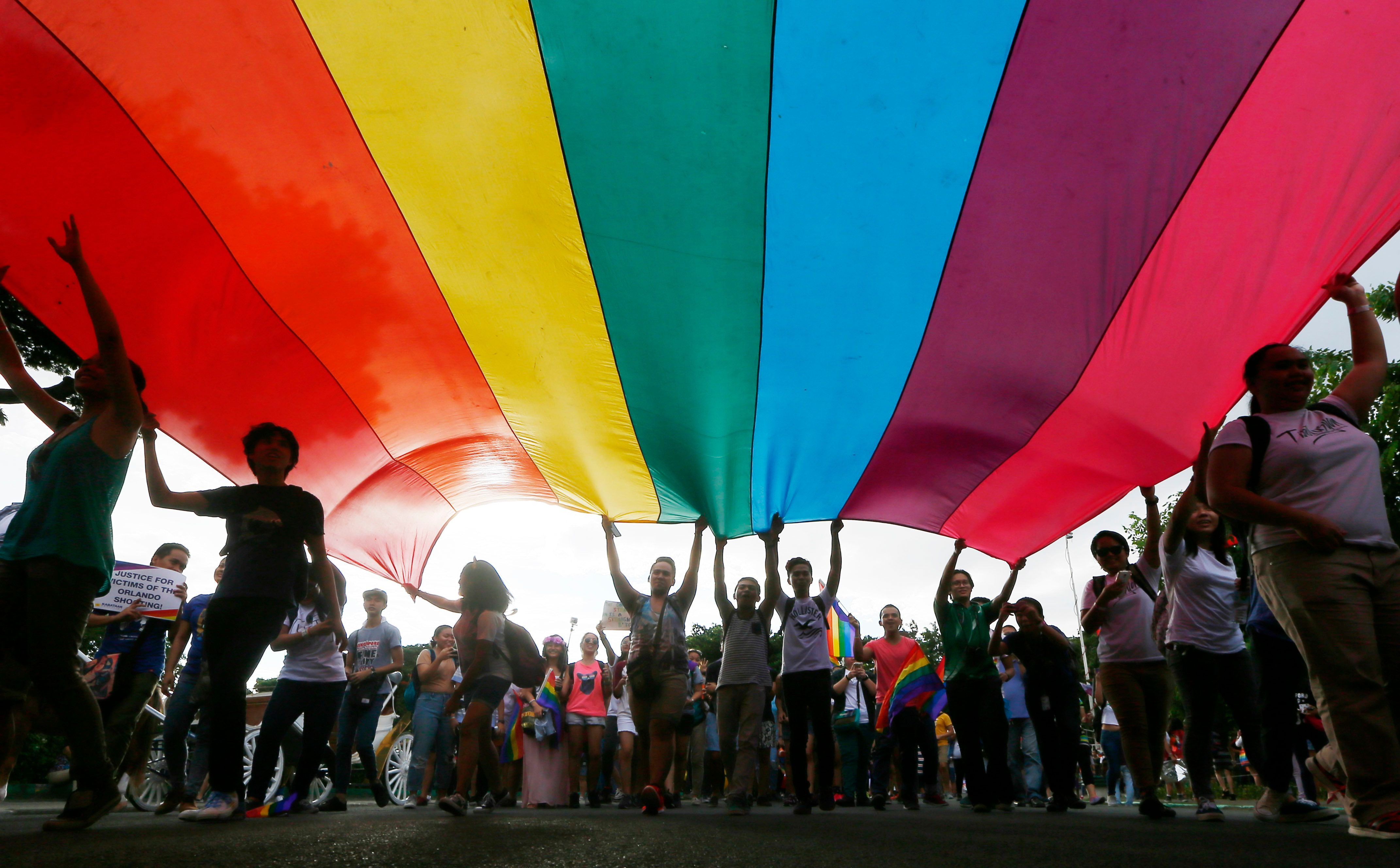 """FILE - In this Saturday, June 25, 2016. file photo, members of LGBT carry a huge rainbow flag as they march around the Rizal Park to celebrate the annual """"Pride March""""in Manila, Philippines. Several LGBT organizations are calling for the passage of an Anti-Discrimination bill that they say would protect the LGBT community .(AP Photo/Bullit Marquez)"""