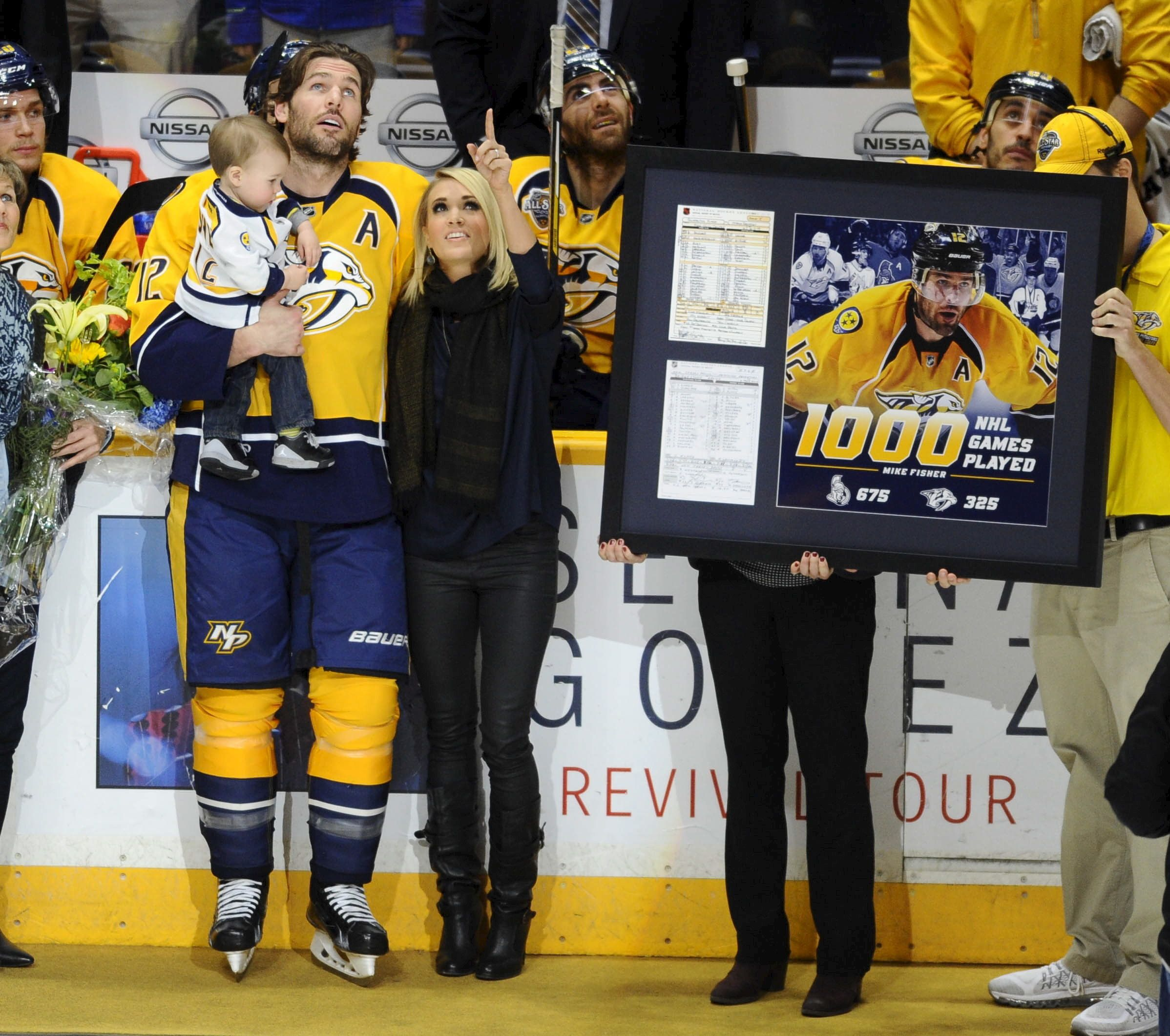 Mar 21, 2016; Nashville, TN, USA; Nashville Predators center Mike Fisher (12) is recognized for his 1000 games played in the NHL with wife Carrie Underwood and son Isaiah at Bridgestone Arena. Mandatory Credit: Christopher Hanewinckel-USA TODAY Sports      TPX IMAGES OF THE DAY