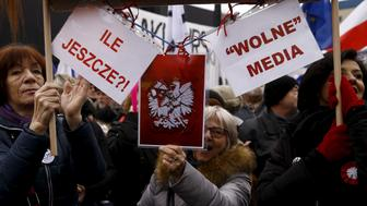 """People gather during an anti-government demonstration for free media in front of the Polish television building in Warsaw, January 9, 2016. The placards read """"How many more?"""" (L) and """"Free Media"""". REUTERS/Kacper Pempel"""