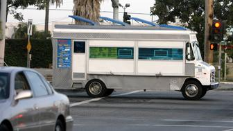 """The """"Mariscos Tatiana"""" taco truck is driven westbound on Venice Blvd. on its way to its location for the night in Los Angeles May 2, 2008. A Los Angeles institution, taco trucks roam the City of Angels selling juicy burritos and spicy $1 tacos filled with pork, beef cheeks or tongue, goat and almost any other meat that can be wrapped in a tortilla and dabbed with hot sauce. The problem is, some don't roam enough. County supervisors last month sparked a save-the-taco-truck movement by raising penalties for caterers parking in one place for more than an hour to up to $1,000 and six months in jail.  Picture taken May 2, 2008. REUTERS/Danny Moloshok (UNITED STATES)"""