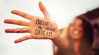 Closeup of a teenage girl's hand with the phrase 'Believe in your Dreams' written in permanent marker on it, with her smiling face blurred in the background