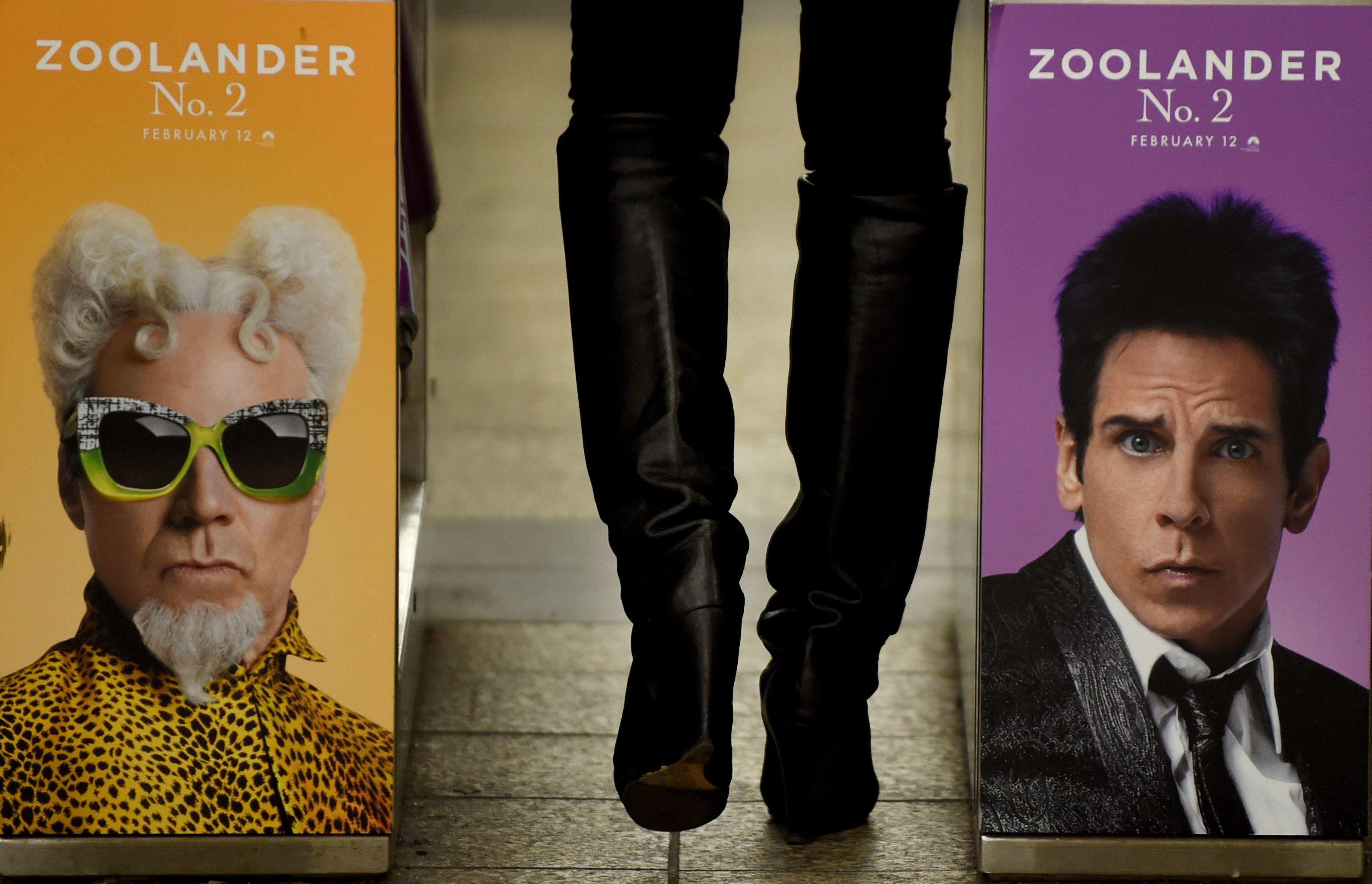 A woman passes through a turnstile on February 25, 2016 in the New York City Subway with a advertisment for 'Zoolander No. 2' featuring Ben Stiller (R) and Will Ferrell. Ads are placed all over the MTA subway system to catch the eye of commuters. / AFP / Timothy A. CLARY        (Photo credit should read TIMOTHY A. CLARY/AFP/Getty Images)