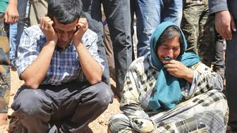 KOBANI, SYRIA - SEPTEMBER 4: Abdullah Kurdi (L), father of Syrian children Aylan, 2, his brother Galip, 3, and husband of Zahin Kurdi, 27, who drowned after their boat sank en route to the Greek islands in the Aegean Sea, mourns during funeral of his family in the Syrian border town of Kobani (Ayn al-Arab) on September 4, 2015. The 12 people, including eight children, drowned after their boat sank en route to the Greek islands in the Aegean Sea. (Photo by Isa Terli/Anadolu Agency/Getty Images)