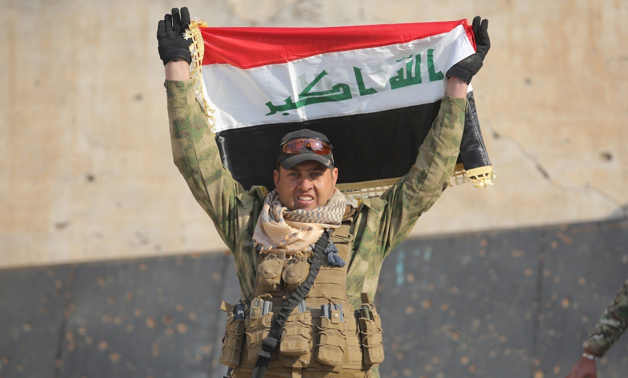 RAMADI, IRAQ - DECEMBER 28: Member of the Iraqi security forces carries a flag of Iraq after retaking Ramadi city from Daesh, in Ramadi, Iraq on December 28, 2015. (Photo by Ali Mohammed/Anadolu Agency/Getty Images)