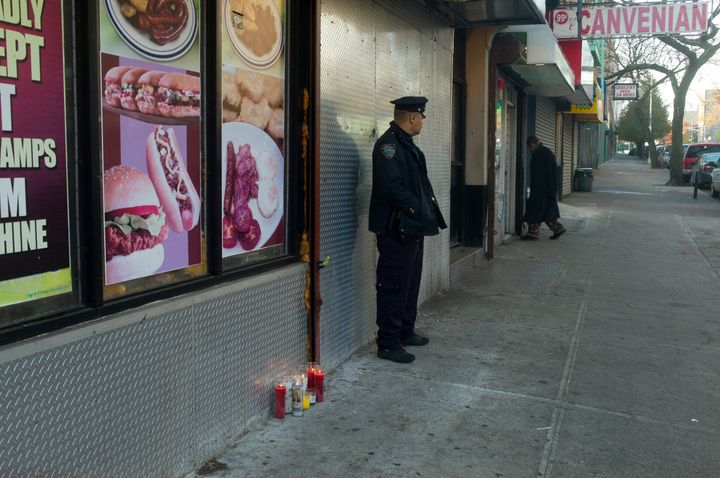 A police officer stationed on the street in the Bronx after a fatal shooting in November.