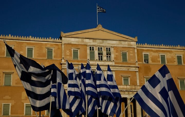 The Greek Parliament is seen behind flags.