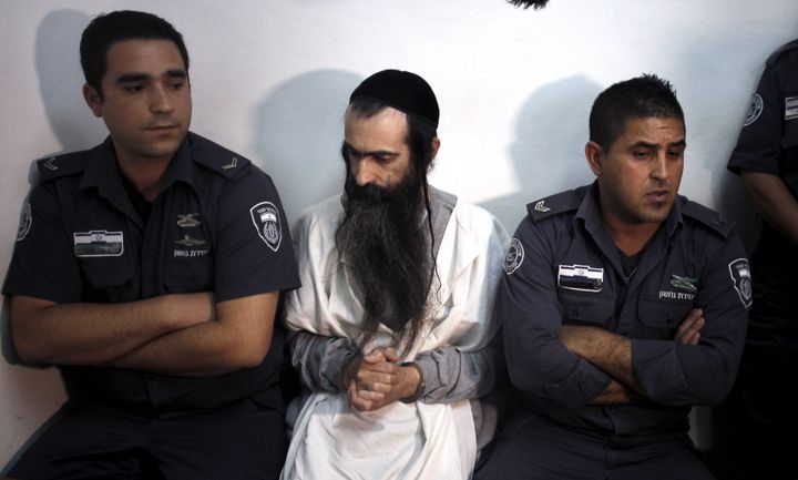 Yishai Schlissel (C) is escorted by security personnel at the Jerusalem Magistrates Court July 31, 2015.