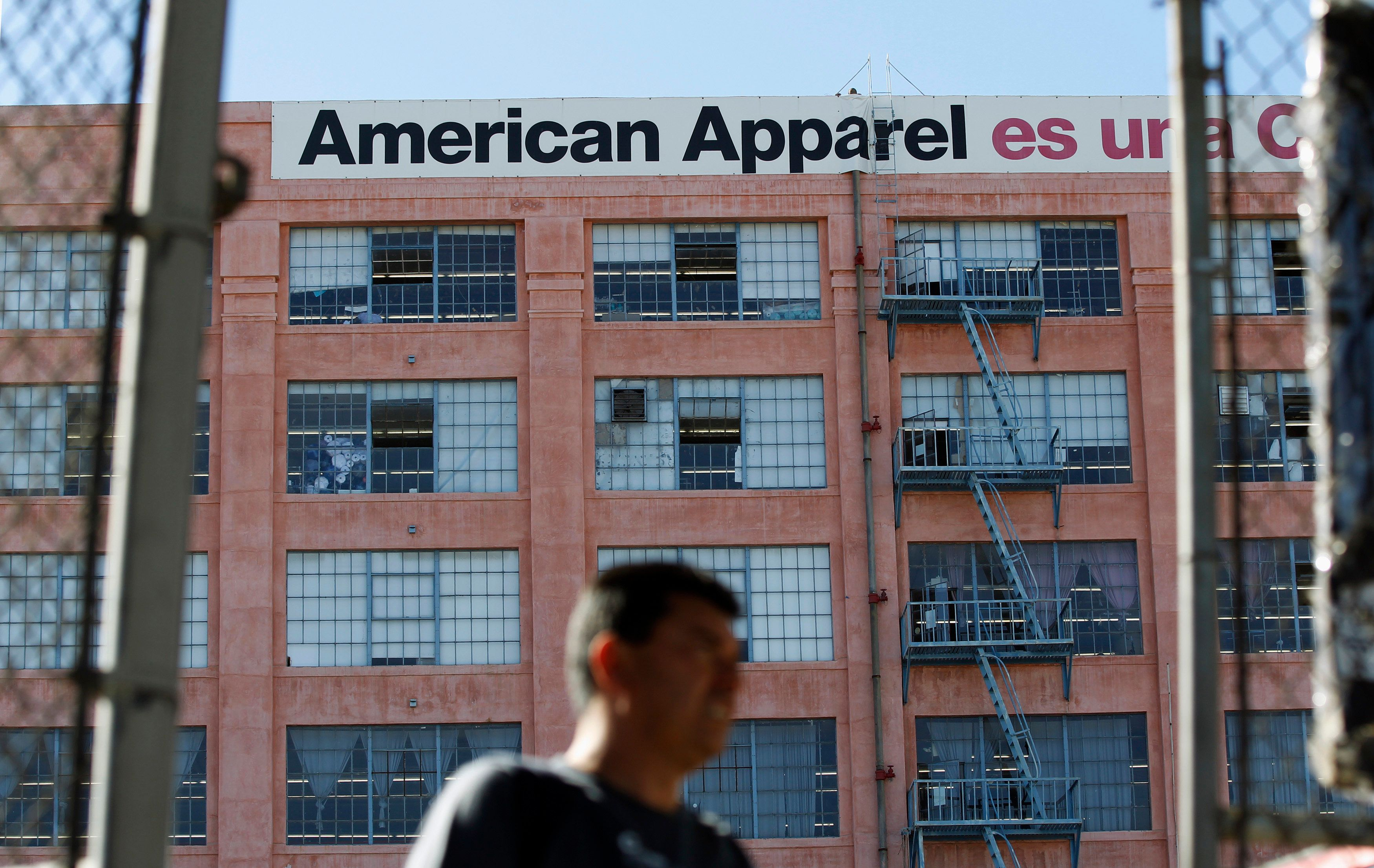 A man walks past the American Apparel headquarters in Los Angeles April 1, 2011. Clothing chain American Apparel, known for racy advertising and its founder's legal problems, may file for bankruptcy if it does not get enough money to keep running, and might even have to liquidate, the company said. REUTERS/Mario Anzuoni (UNITED STATES - Tags: BUSINESS)