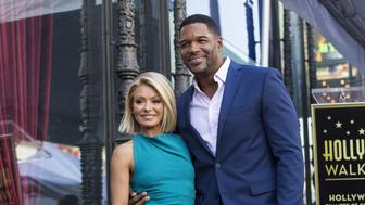 Television personality Kelly Ripa poses on her star with former professional American football player Michael Strahan after it was unveiled on the Hollywood Walk of Fame in Los Angeles, California October 12, 2015.  REUTERS/Mario Anzuoni