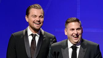 Actors Leonardo DiCaprio (L) and Jonah Hill (R) invite Martin Scorsese to the podium to present him with the Cinematic Imagery Award during the 18th Annual Art Directors Guild Excellence in Production Design Awards in Beverly Hills, California February 8, 2014. REUTERS/Kevork Djansezian (UNITED STATES - Tags: ENTERTAINMENT)