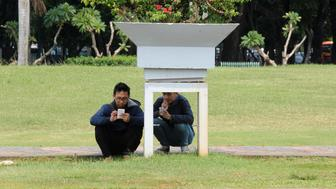 People play the mobile phone game Pokemon GO in a park in Central Jakarta, Indonesia July 21, 2016. REUTERS/Iqro Rinaldi