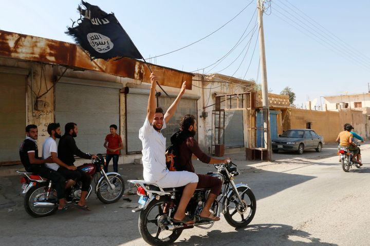 A resident of Tabqa city touring the streets on a motorcycle waves an Islamist flag in celebration after Islamic State milita