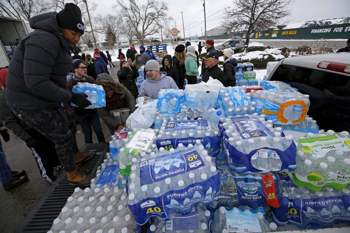 Volunteers distribute bottled water to help combat the effects of the crisis when the city's drinking water became contaminat