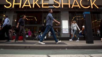 People walk past a Shake Shack restaurant in the Manhattan borough of New York August 15, 2014. Shake Shack, the fast-food restaurant chain famous for its hamburgers and milkshakes, is preparing to go public, seeking to tap stock market demand for popular casual dining companies,  according to people familiar with the matter. To match Exclusive SHAKESHACK-IPO/ REUTERS/Carlo Allegri (UNITED STATES - Tags: BUSINESS FOOD)