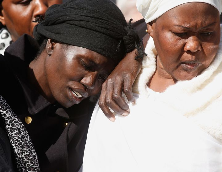 Akon Guode collapses against at friend during the funeral for her three children in 2015.