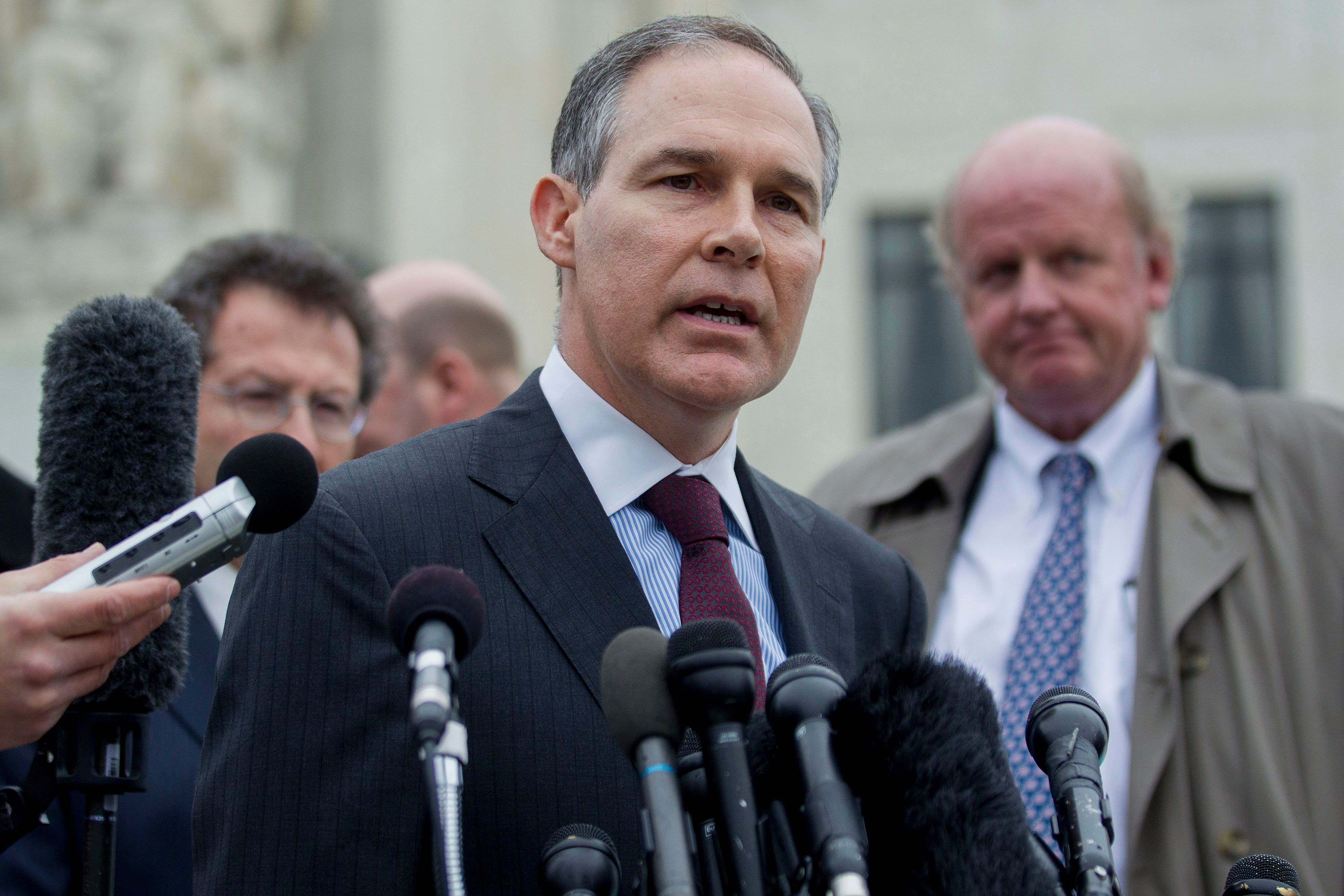 Scott Pruitt, attorney general of Oklahoma, center, speaks to the media in front of the U.S. Supreme Court with Michael Carvin, lead attorney for the petitioners and partner at Jones Day, right, and Sam Kazman, general counsel with the Competitive Enterprise Institute, left, in Washington, D.C., U.S., on Wednesday, March 4, 2015. A U.S. Supreme Court argument over Obamacare's tax subsidies divided the justices along ideological lines, potentially leaving two pivotal justices to decide the law's fate. Photographer: Andrew Harrer/Bloomberg via Getty Images