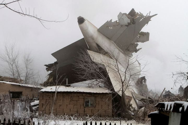 The plane's tail atop a house.