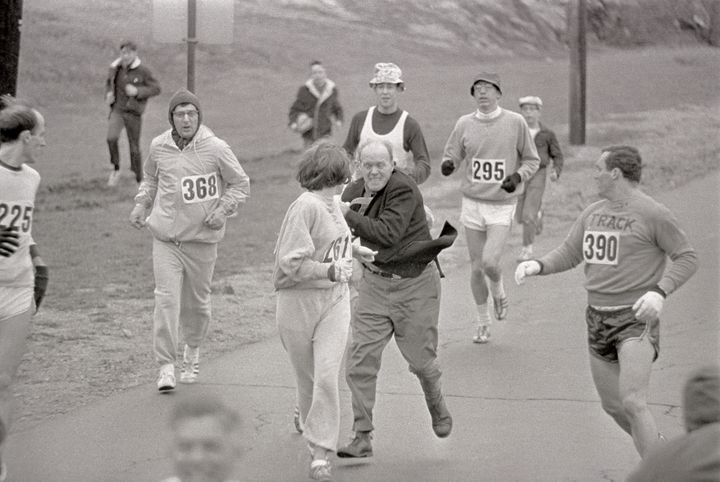 Trainer Jock Semple (in street clothes) enters the field of runners to try to pull Kathy Switzer out of the race.