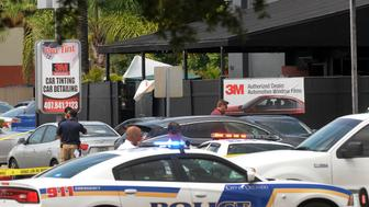 ORLANDO, FLORIDA - JUNE 12:  Orlando police officers seen outside at the main entrance of Pulse nightclub (black building behind) after a fatal shooting and hostage situation on June 12, 2016 in Orlando, Florida. The suspected shooter, Omar Mateen, was shot and killed by police. 50 people are reported dead and 53 were injured. (Photo by Gerardo Mora/Getty Images)